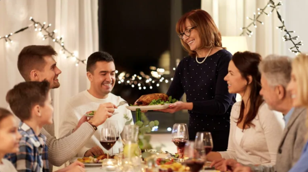 Family passing holiday food around the table